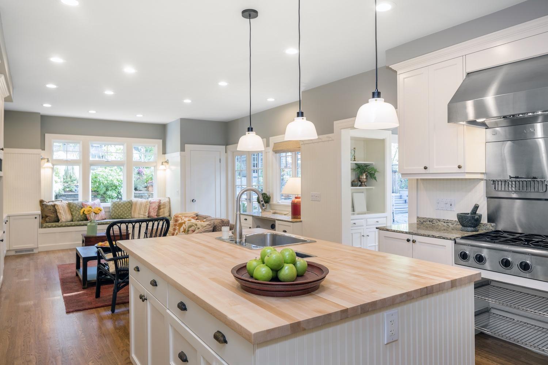 Luxury Kitchen Interior in white with wooden floor and kitchen island.
